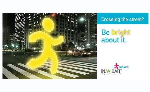 Poster: Main image of a fluorescent stick figure crossing at an intersection. INavigate logo. Text: Crossing the street? Be bright about it.