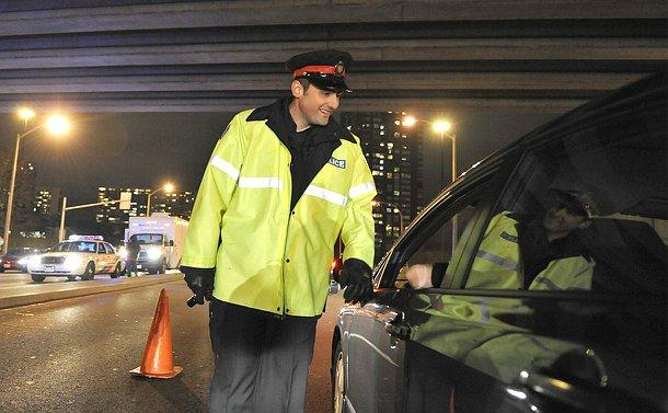 A man in TPS uniform leans in towards an open car window