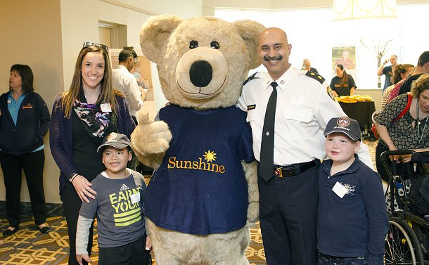 Woman and a young boy, and man in a police uniform with another young boy, flank a bear mascot wearing a Sunshine shirt