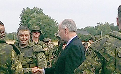 A man in a suit shakes hands with a man in army fatigues