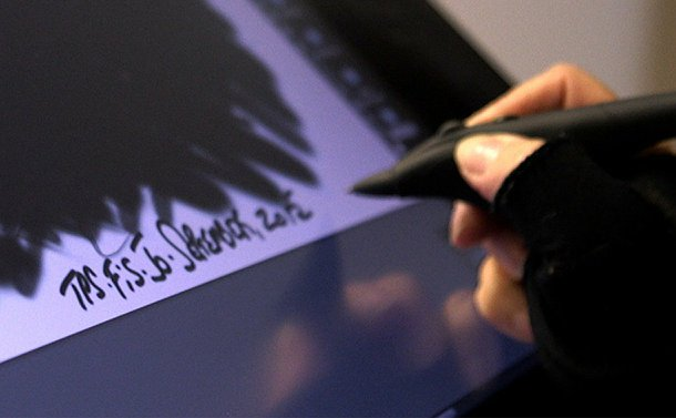 A hands with a stylus over a monitor with a signature