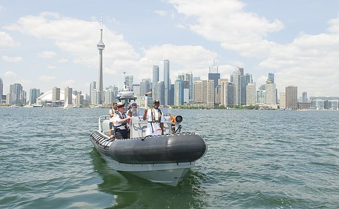 A man holding a torch on a boat with Toronto skyline in background