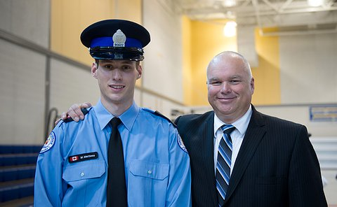 A man in a court officer uniform with his father by his side who is wearing a suit and has his arm around his son.