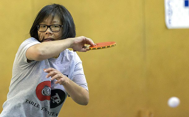A woman holding a table tennis racket with the ball near the racket