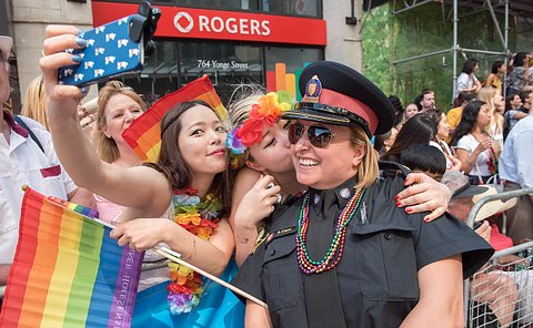 A woman in TPS uniform takes a selfie with two other women