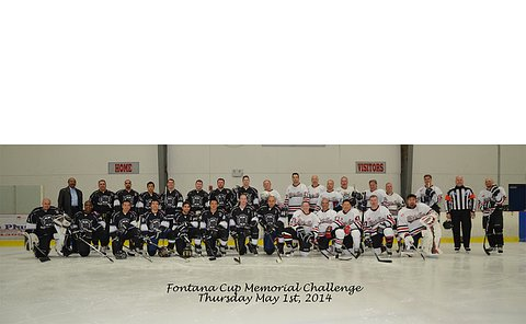 A large group of hockey players pose on the ice