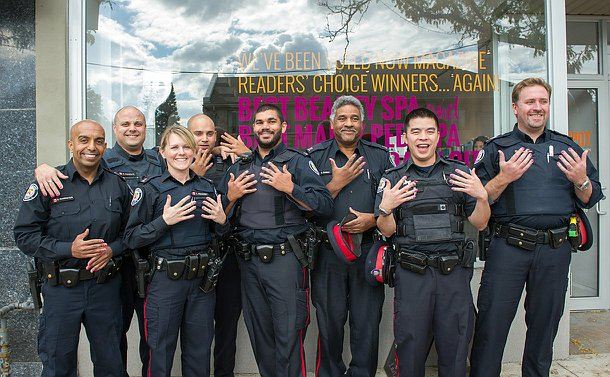 Officers in uniform and pink painted nails stand outside a nail salon.