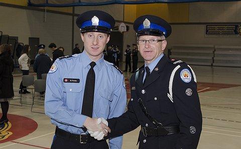 Two men in TPS Court Officer uniform shaking hands