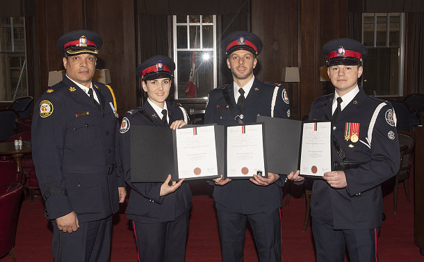 One woman and three men in TPS uniform