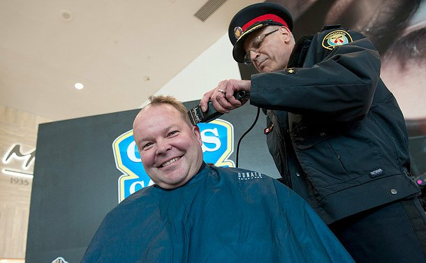 A man wearing a hairdresser gown smiling at the camera as his head is being shaved by a man in a Toronto police uniform.