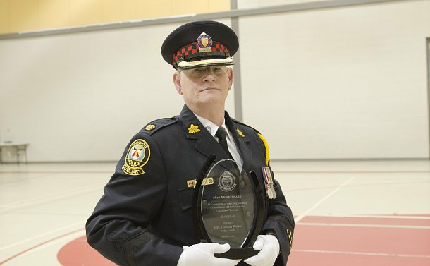 A man in TPS Auxiliary uniform holding an award