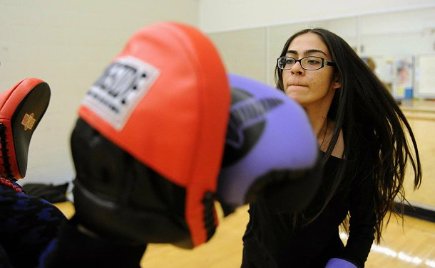 A girl in boxing gloves punching pads