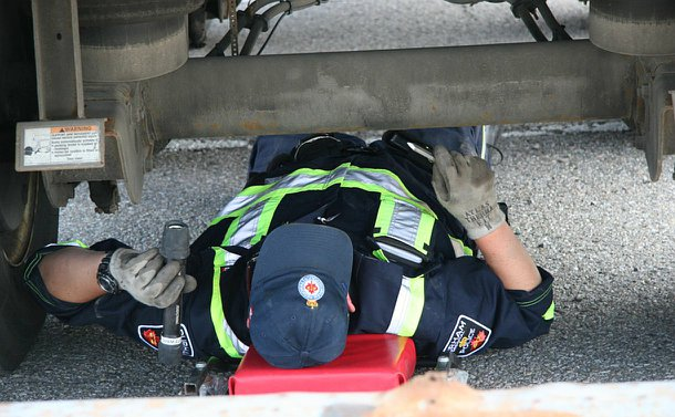 A man in overalls points a flashlight at a vehicle under carriage while lying on his back