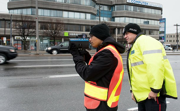 An officer in a bright police rain parka standing behind a student who is holding up a radar gun and looking through it.