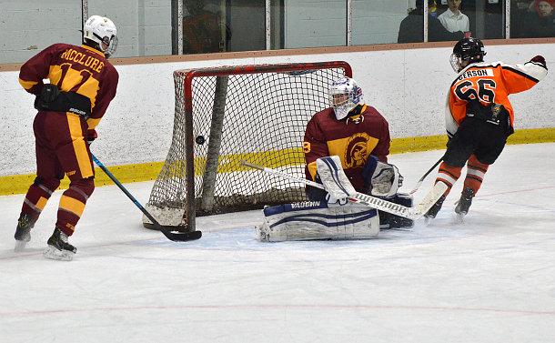 A hockey goalkeeper watching a puck go into the net