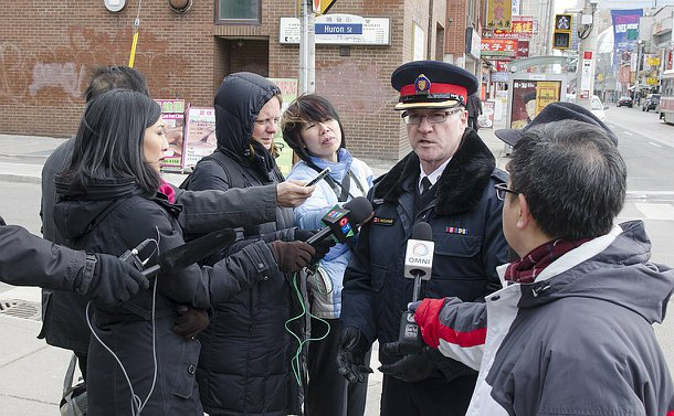 A group of reporters interviews a man in TPS uniform