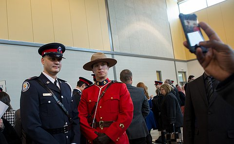 A man in TPS uniform along with an RCMP officer in uniform