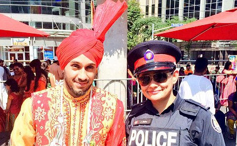 An officer next to a man in traditional indian wear.