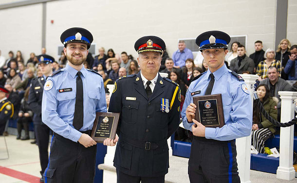 Two men in special constable uniform holding plaques with a man in police uniform