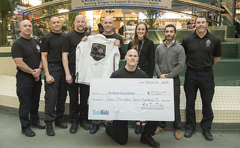 A group of poeple with a large cheque