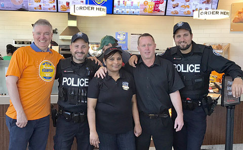 Two men in TPS uniform with Tim Hortons staff