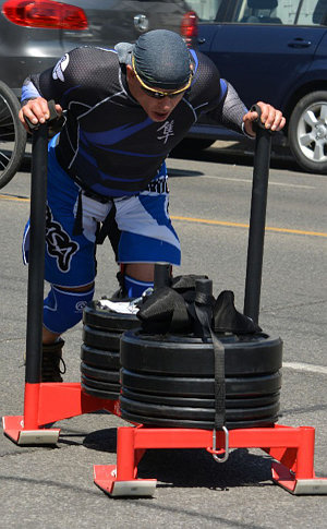 Man in a blue sports outfit pushing a red metal sled loaded with weights