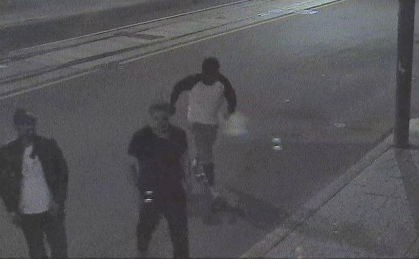 Three men walking on a street