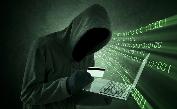 A hooded figure holding a credit card and laptop computer with numbers in background