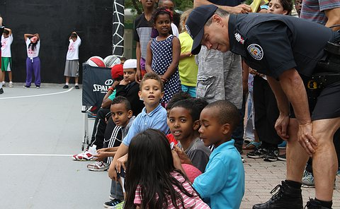 A man in TPS uniform leans over a group of children