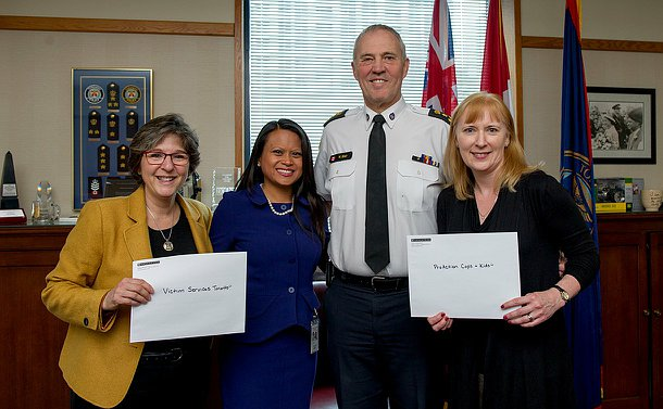 Three women and the chief posing with two cheques