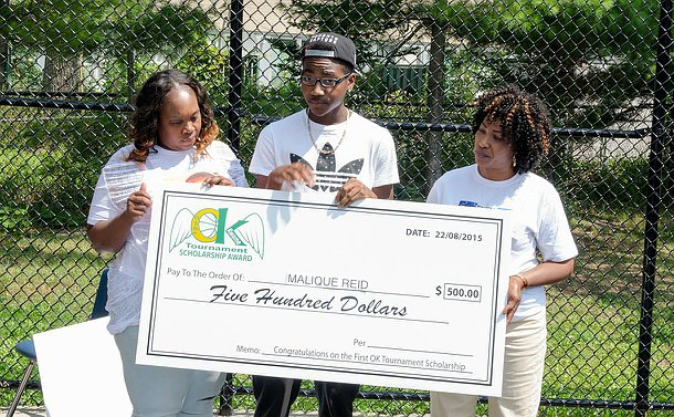 Two women and a boy hold up a cheque for five hundred dollars, they are standing outside in a park