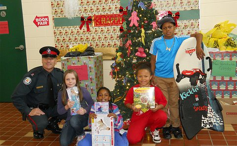 A man in TPS uniform with boys and girls holding toys beside a Christmas tree