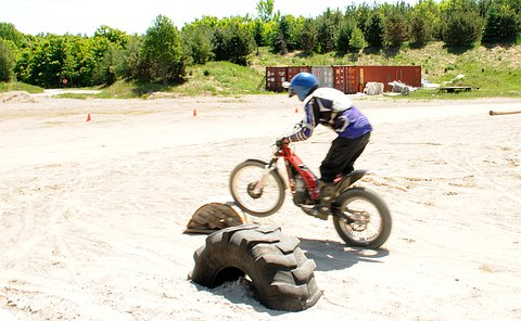 A boy on a dirt bike has his front tire on top of a large tire partially buried in dirt