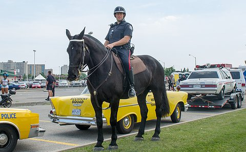 A Toronto Police Officer on a horse, behind him is a vintage yellow police car.