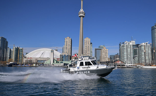 A TPS boat on the water with the skyline in the background