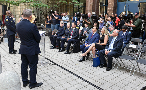 News reporters with cameras, men and women in dress attire and police uniforms sitting in front of a building entrance