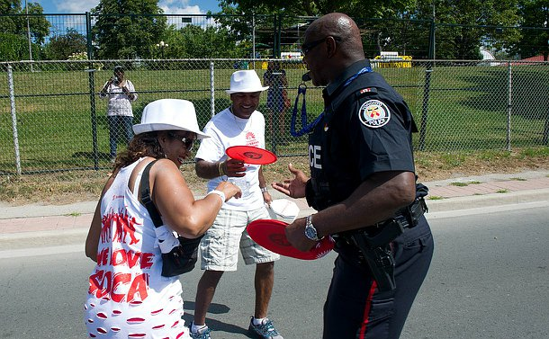 An officer in uniform handing out a frisbee to a man and a woman who are smiling.