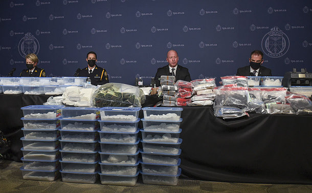 A group of people seated at table with drugs packaged in plastic bags and bins