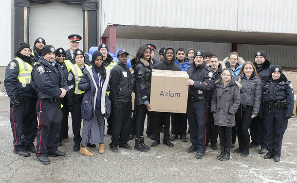 A large group of people, including men and women in TPS uniform in front of a loading dock