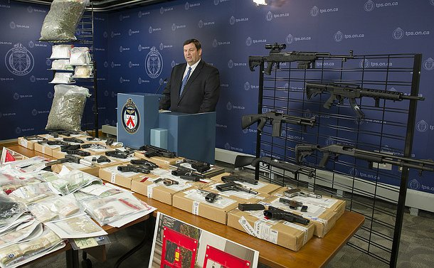A man at a podium near two racks holding plastic bags with powders and marinjuana and guns. A table in front of him has guns on boxes and cash in plastic bags