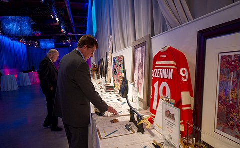 A man looking at a table with different items including a hockey jersey and a painting.