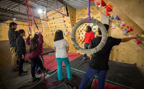 A group of young people stand around a man talking beside a climbing wall