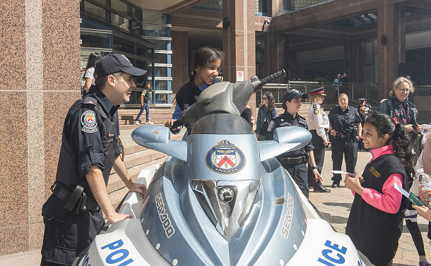 A child on a Sea Doo beside an auxiliary officer