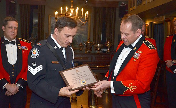 A man in TPS uniform is handed a plaque by a man in military dress uniform