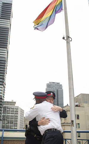 Two men in TPS uniform hug under a flag
