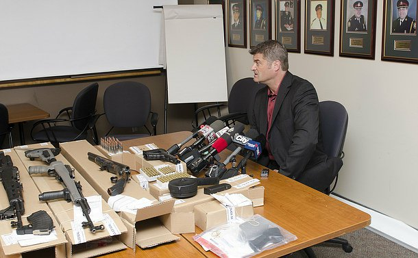 A man sits beside a table with microphones and firearms and bullets laid out across it