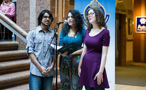 A man and two women sing into one microphone