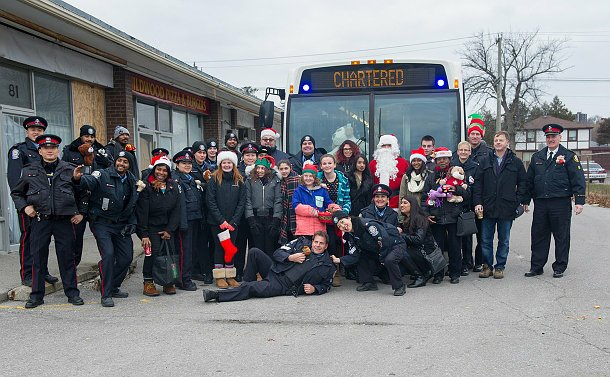 "A group of people standing in front of a TTC bus that reads ""chartered"""