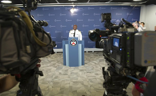 A man in TPS uniform at a podium in front of video cameras