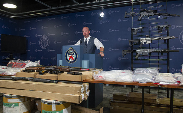 A man at a podium behind tables with firearms and drugs